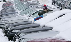 An employee shovels snow off cars at a Saab dealership in Concord, N.H.