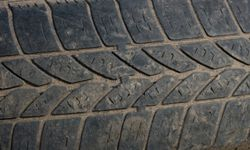 Evidence of flat rubber bars running perpendicular to the direction of the tread indicate you need new tires.