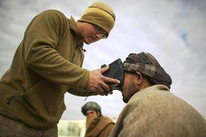 A Marine uses a SEEK II device to take a biometric picture of an Afghan man.