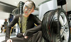 A model with face paint of tire marks on his face poses next a real tire at the Auto Shanghai 2005 exhibition in Shanghai, China.