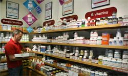 Don Olufs stocks shelves with vitamins at Vibrant Health in San Francisco. In bad economies, Americans may buy more vitamins in an attempt to keep more than just their nails healthy.
