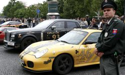 A Slovakian policeman stands next to the cars of Gumball 3000 rally competitors in front of The Carlton hotel on May 4, 2007, in Bratislava, Slovakia.