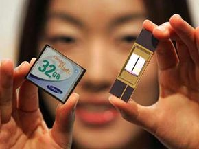 An employee of Samsung Electronics shows a 32-Gigabyte NAND memory card and chip. See more computer memory pictures.